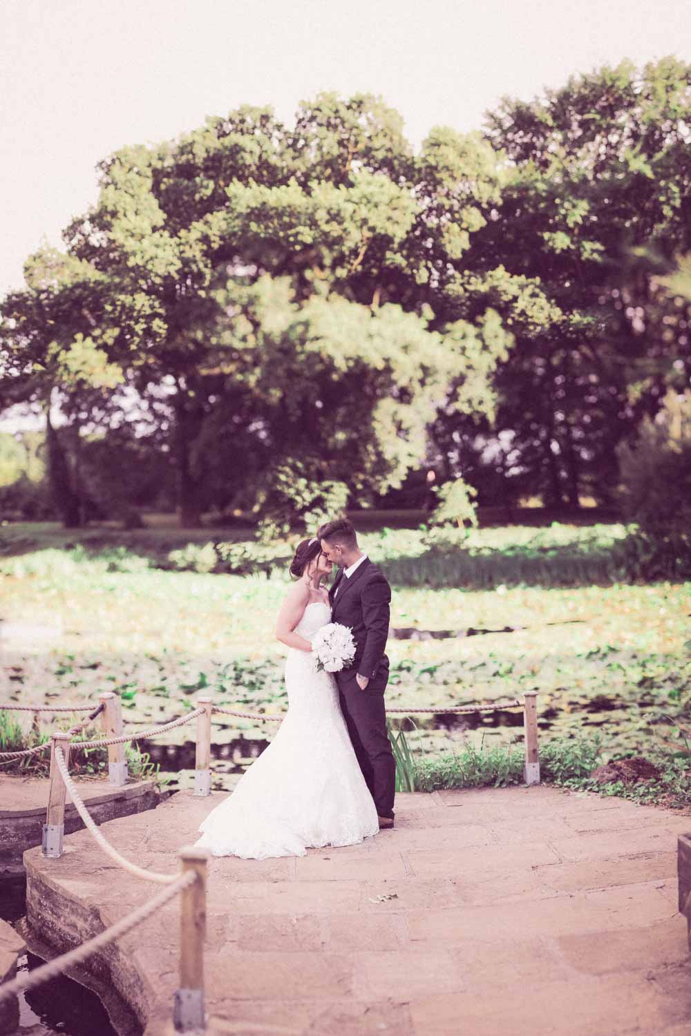 Newlyweds embrace in front of a pond with green lilies and trees at Cave Castle