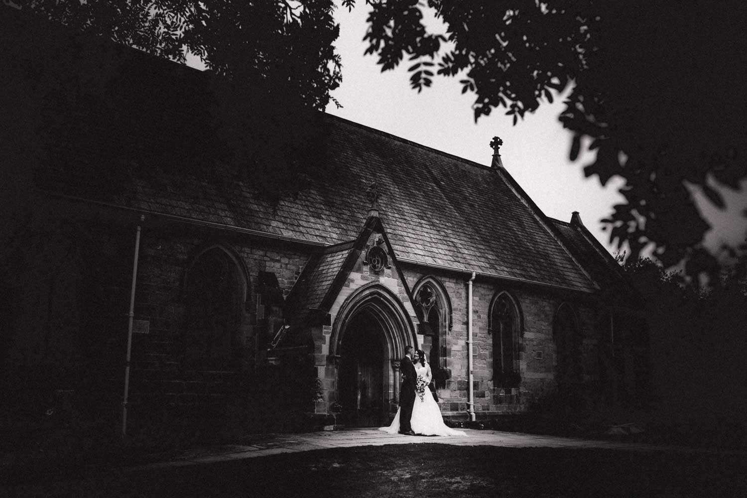 Newlywed couple arm in arm outside the church alone together