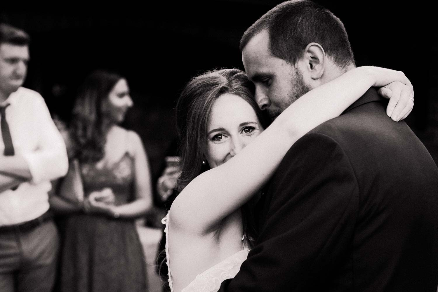 Newlywed couple embraced in first dance, wife turns and looks at camera.
