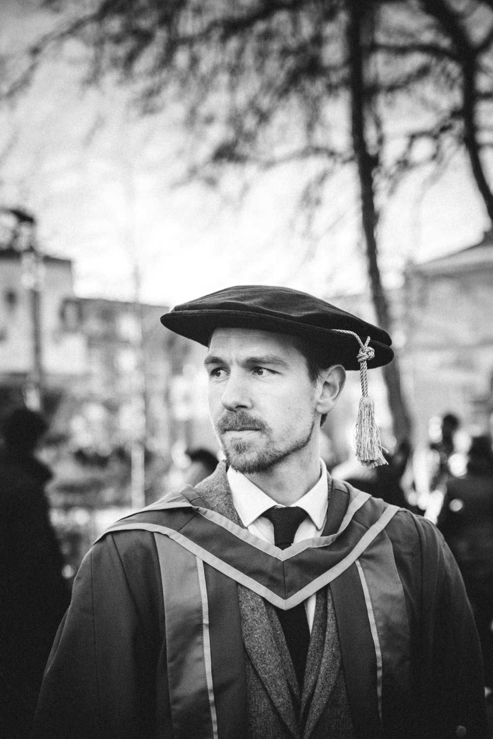 Young man wears his Ph.D graduating gown and hat staring into the distance
