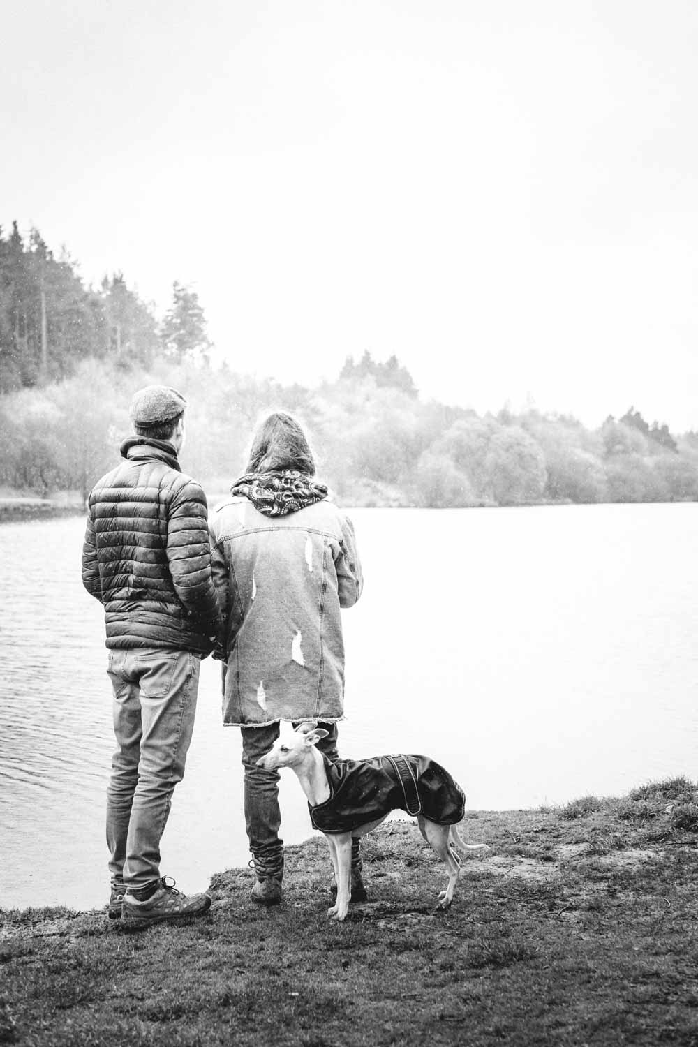 Young couple stand on the bank of a reservoir looking out across water with Whippet in a coat behind them