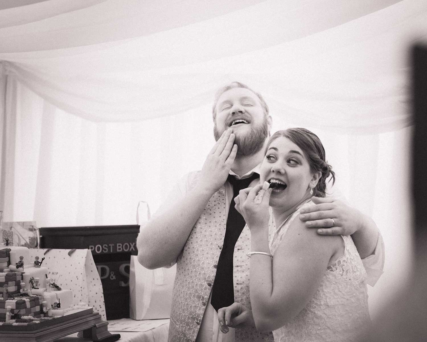Newlyweds try a piece of their wedding cake and look very happy whilst doing so