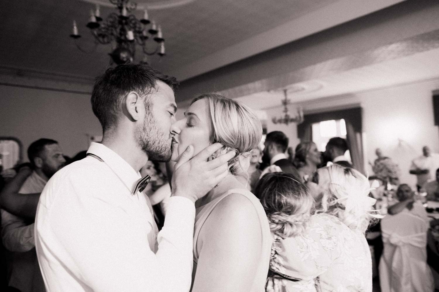 Young couple kiss, surrounded by guests on packed dance floor whilst a tear runs down her cheek
