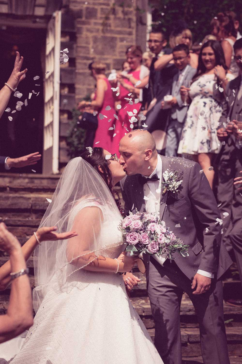 Newlyweds pause for kiss outside whilst walking down steps as guests through confetti over them