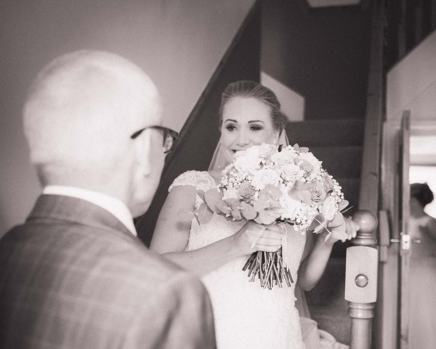 Young bride in wedding dress walks down stairs to father with tears in her eyes