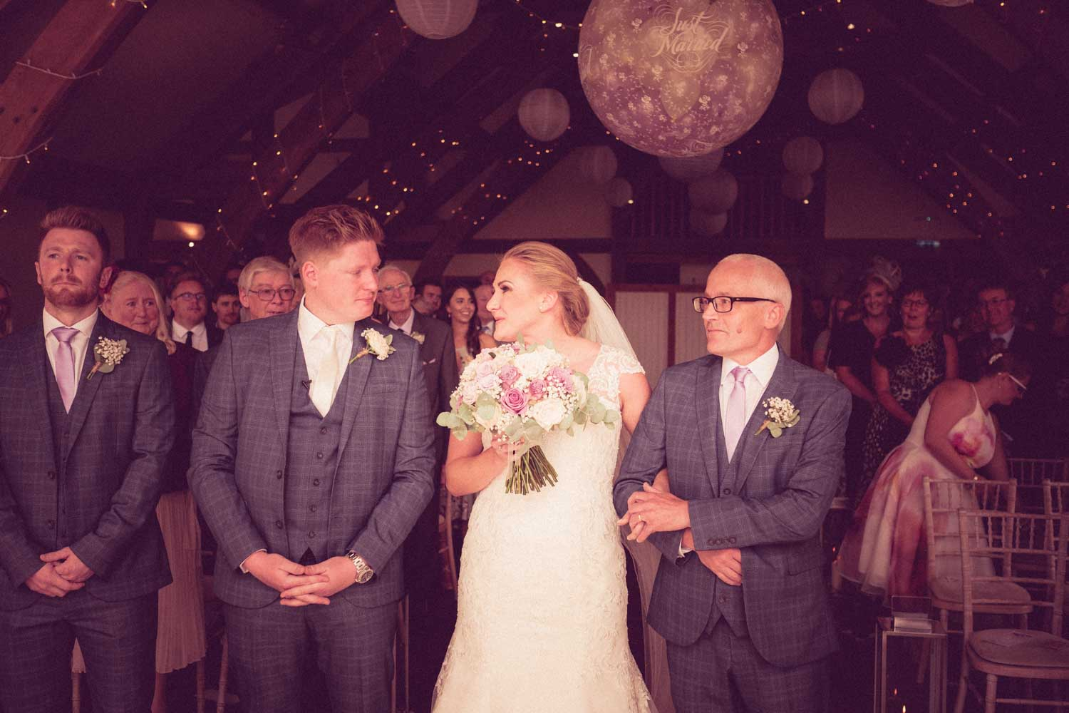Bride arm in arm with Bride's father reach end of aisle, groom and bride share a quick glance