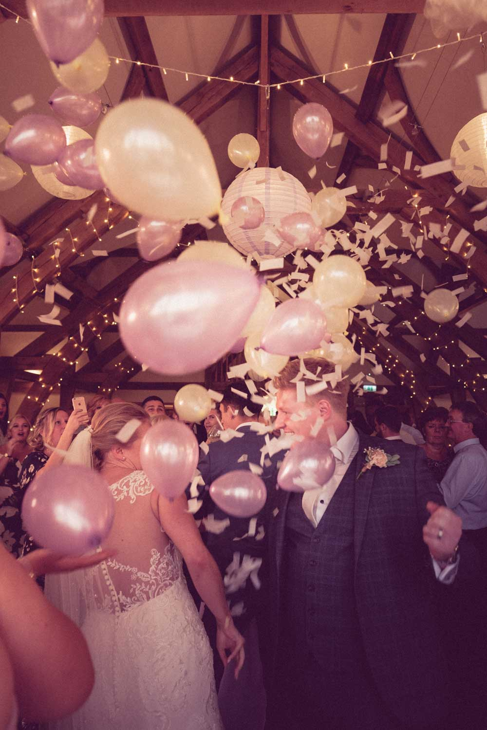 Balloon pops above newlyweds first dance dropping hundreds of smaller balloons on them