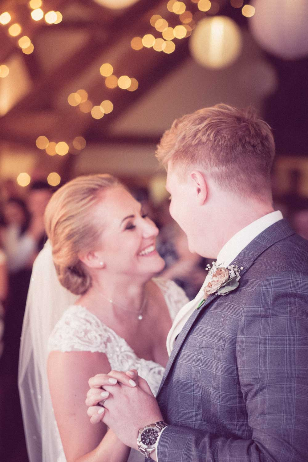 Newlyweds enjoy first dance whilst bride smiles lovingly at groom