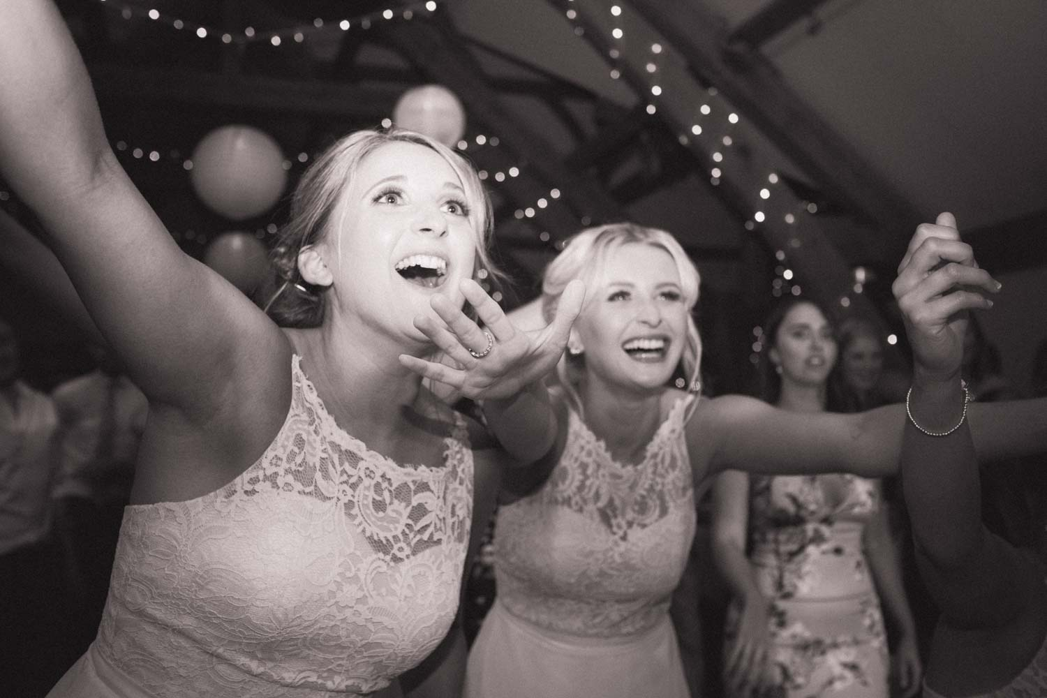 Bridesmaids lean forward arms stretched out and smile whilst dancing