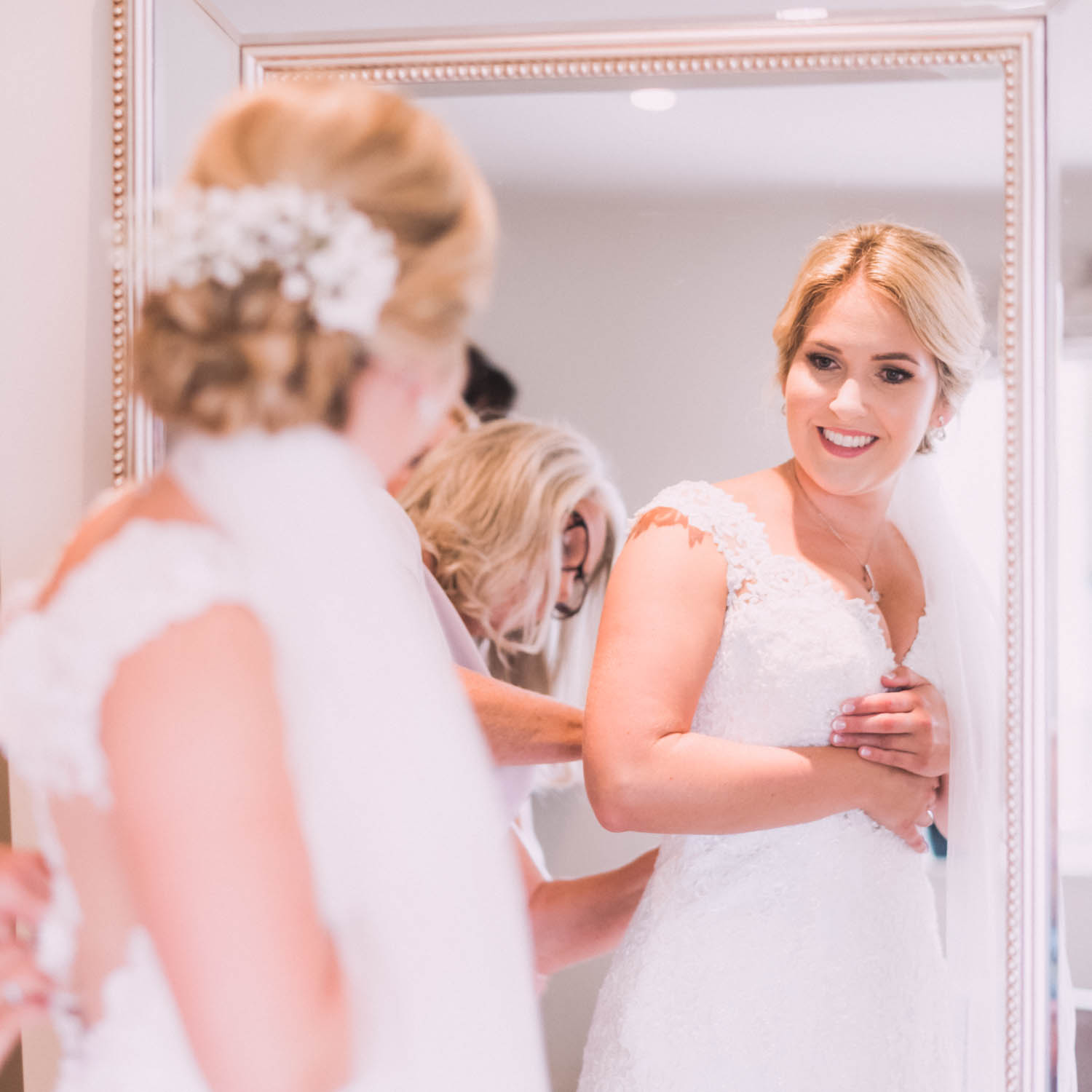 Bride looks at self in mirror and smiles whilst mother fastens her wedding dress