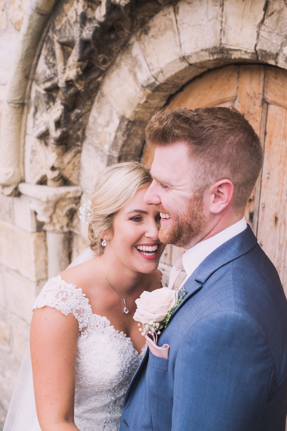 Newlywed couple enjoy a laugh in each others' arms at Priory Cottages and Barn