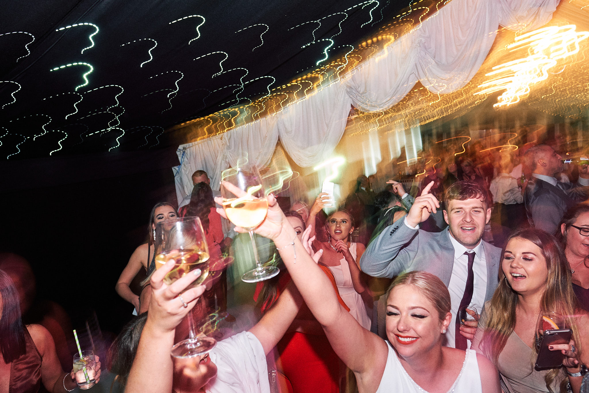 Wedding guests enjoy the evening dancing whilst light streaks across the image